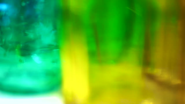 Colorful glass bottles and vases. Close up abstract vivid rainbow color material video