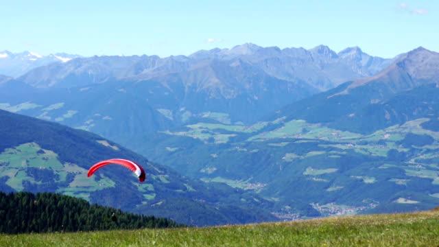 colorato deltaplano nel cielo sopra montagne kronplatz, italia - volo con parapendio video stock e b–roll