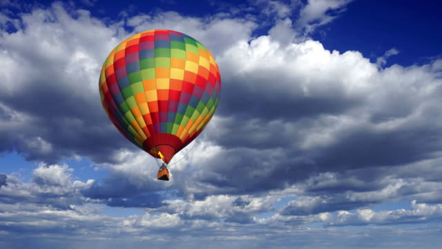 A colorful hot air balloon coming closer against a fluffy clouds time lapse sky