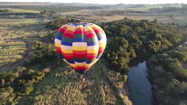 Colorful hot air balloon flying over countryside and river. Great landscape.