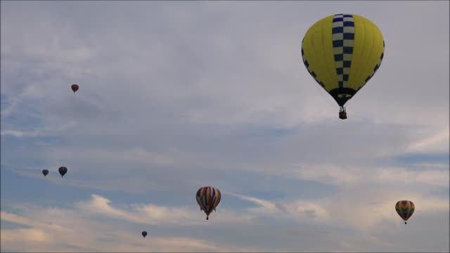 Colorful hot air balloons float peacefully in sky at dusk video