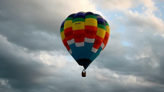 renkli sıcak hava balonları bulutlara karşı yavaş yavaş yükselen üzerinde uçan. seyahat, macera, festival. - zeplin stok videoları ve detay görüntü çekimi