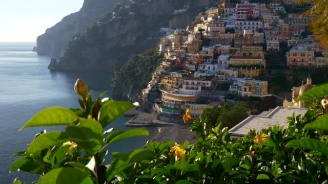 colorful houses on a tyrrhenian sea coast seen through green juicy flora in positano, italy. positano is a village in naples metropolitan area. uhd 4k - italian architecture stock videos & royalty-free footage