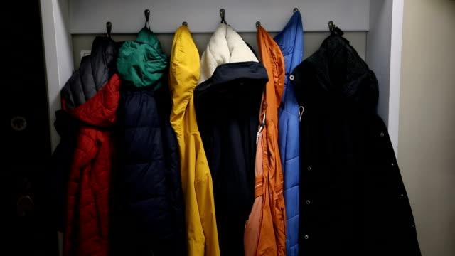giacche colorate su appendiabiti - abiti pesanti video stock e b–roll