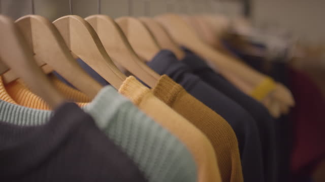 colorful jumpers on hangers - спортивная одежда стоковые видео и кадры b-roll