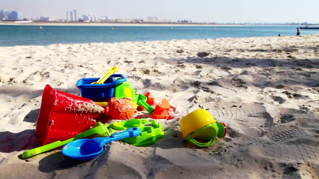 Colorful kids toys on sand beach video