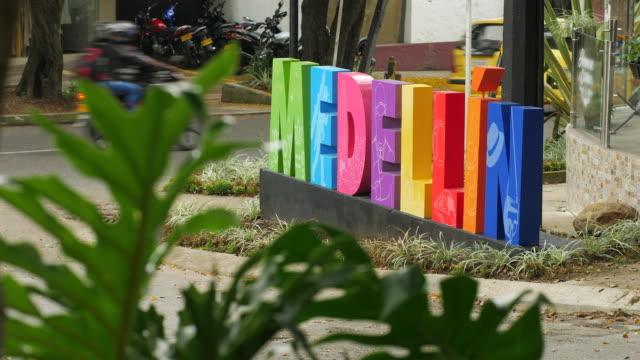 vídeos de stock, filmes e b-roll de sinal de medellin colorido na rua com tráfego e folhas verdes - colômbia