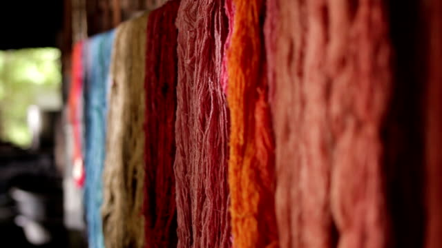 Colorful of raw silk thread on a rail. video