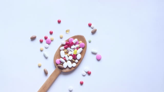 colorful pills on spoon on white background - antidolorifico video stock e b–roll