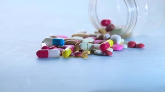 stockvideo's en b-roll-footage met kleurrijke pillen die van een container op lijst morsen - doordrukstrip