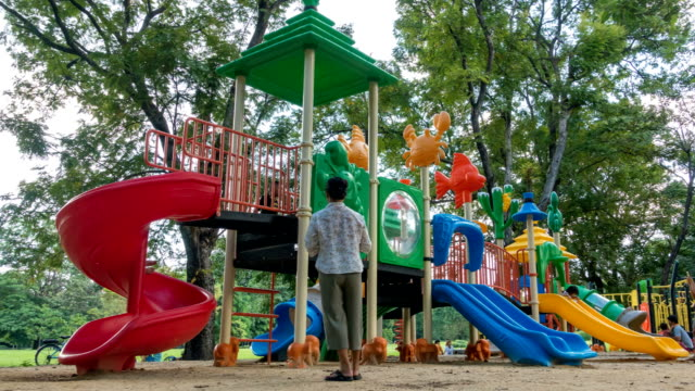 bunter spielplatz mit kindern und eltern im park - kinderspielplatz stock-videos und b-roll-filmmaterial