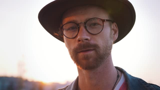 Colorful portrait of young stylish guy with red beard in glasses and in hat looking at camera during sunset outdoors. Cinematic shot video