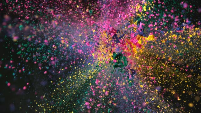 vídeos de stock e filmes b-roll de colorful powder exploding on black background in super slow motion - laranja cores