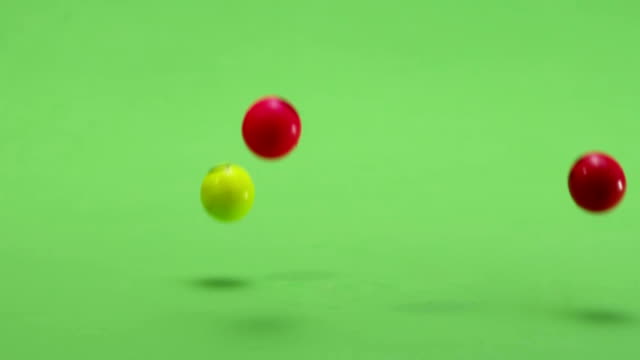 Colorful smile balls falling into green surface . Slow Motion. Few shots. video