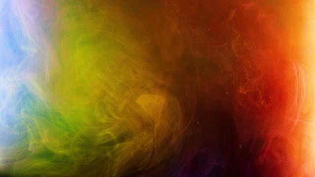 bunte rauchige fluss von gemischten farben in wasser. stock-footage. diffusion von mehrfarbiger tinte mit pailletten in wasser. makrofotografie von farbströmen - kurzwaren stock-videos und b-roll-filmmaterial