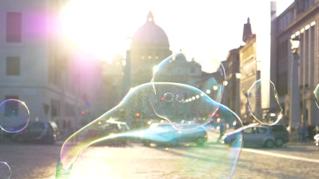 lens flare: colorful soap bubbles fly around the sunlit square in vatican city. - мыло стоковые видео и кадры b-roll