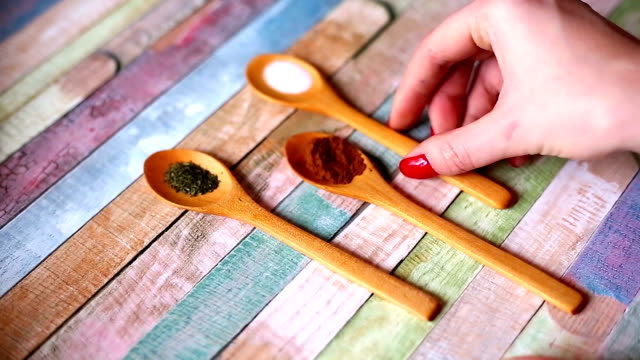 Especiarias coloridas em colheres de madeira - vídeo