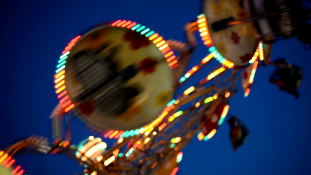 colorful spinning wheel in amusement park at night - adrenalina video stock e b–roll