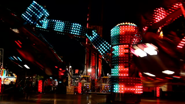 colorful spinning wheel in amusement park at night - luna park video stock e b–roll