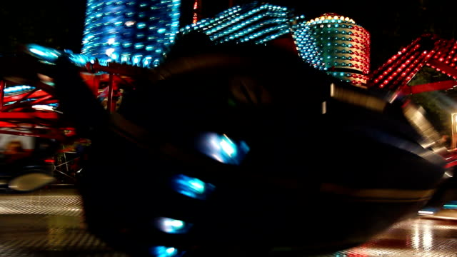 Colorful spinning wheel in amusement park at night video