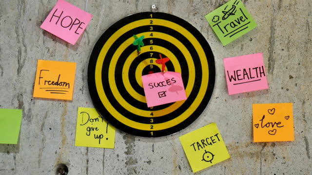Colorful sticky notes with dart game on cement wall, business concept. video