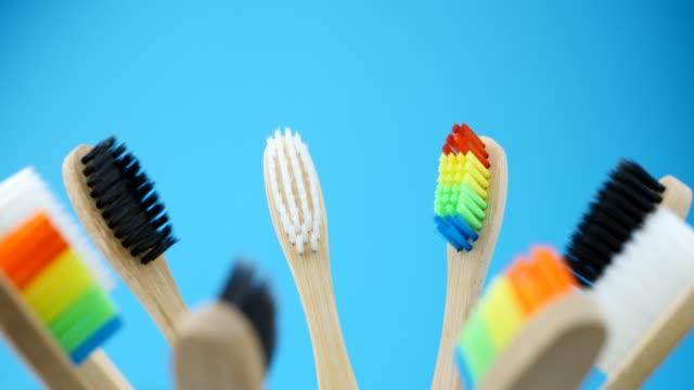 vídeos de stock e filmes b-roll de colorful toothbrushes is spinning on blue background - escovar