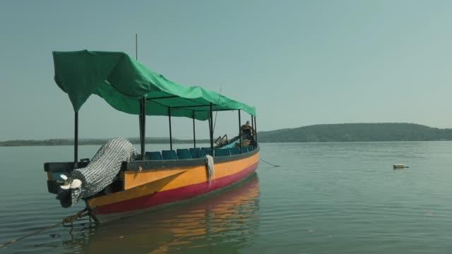 vídeos de stock, filmes e b-roll de barco turístico colorido no mar. barco turístico brilhante com pessoa a bordo flutuando na água do mar calmo contra céu azul sem nuvens em dia ensolarado no resort - equipamento de esporte aquático