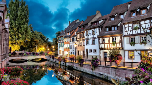 Colorful traditional french houses on the side of river Colorful traditional french houses on the side of river in the evening in Colmar, France (static image with animated sky and water) high dynamic range imaging stock videos & royalty-free footage