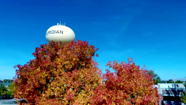 Colorful trees in autumn and yellow water tower with race track video