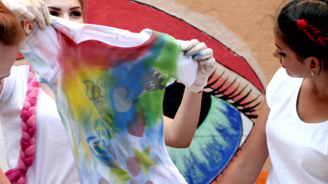 colorful t-shirts with short sleeves in hands girls outdoors, clothes with different colors in arms young woman