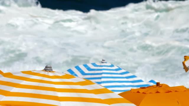 bunte sonnenschirme am strand, mit blick auf mächtige wellen - sonnenschirm stock-videos und b-roll-filmmaterial