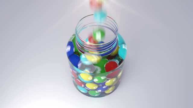 Colorful vitamins fall into the small bottle video