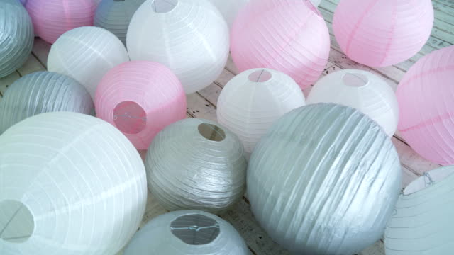 Colorful white pink gray paper lanterns set on floor. video