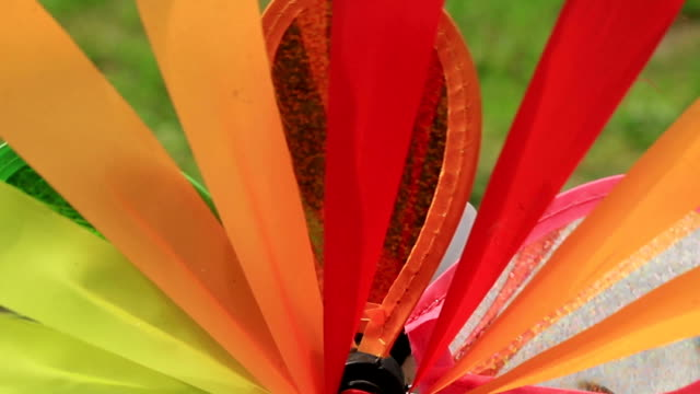 Colorful wind spinner rotates fast, close-up. Garden decoration