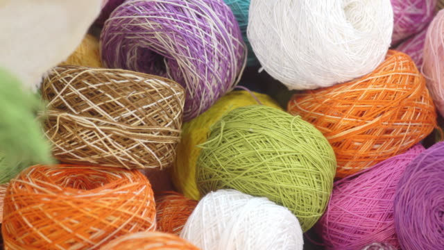 Colorful yarn balls of wool thread for knitting in the basket.
