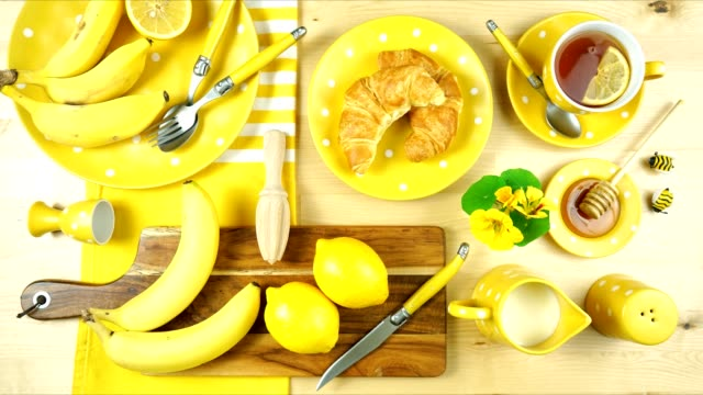 Colorful yellow theme breakfast brunch table setting flatlay stop motion. Modern bright colorful yellow theme morning breakfast or brunch table setting, flat lay stop motion. table top view stock videos & royalty-free footage
