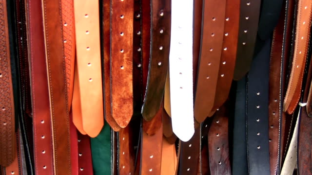 Coloured colored leather belts on display video