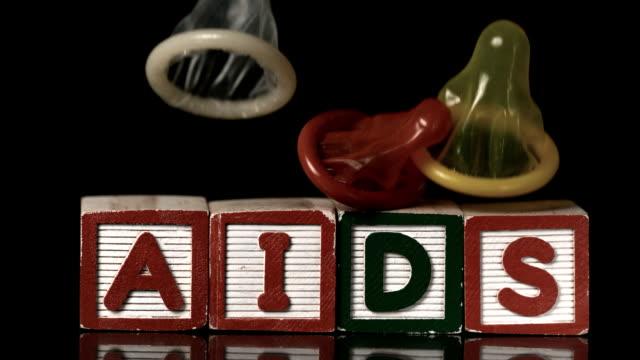 Coloured condoms falling on blocks spelling aids video