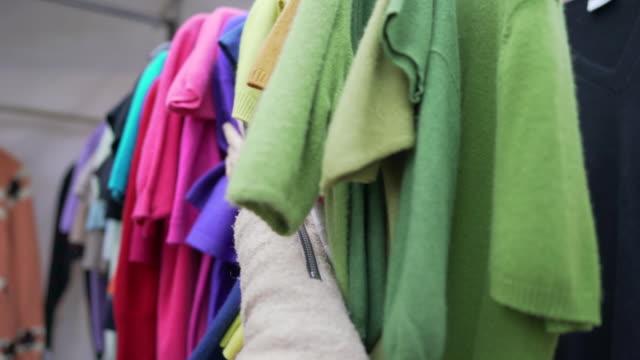 vidéos et rushes de pulls en cachemire colorés de 2ème main à vendre sur un étal de marché à portobello road - mode londres