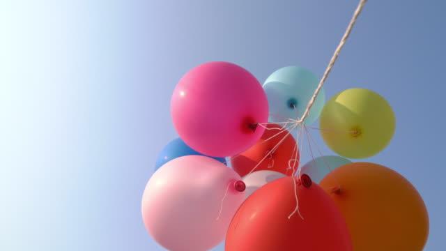 vídeos de stock, filmes e b-roll de balões coloridos voando no ar com céu azul - punhado