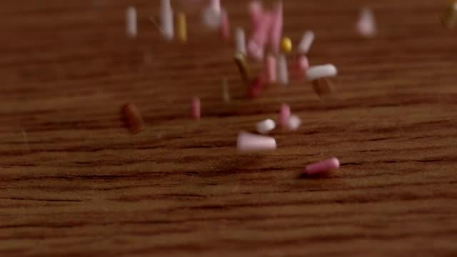 colourful sprinkles pouring onto surface - confetti bildbanksvideor och videomaterial från bakom kulisserna