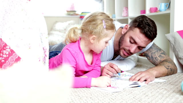 Colouring in with Daddy Father enjoys colouring in with his little girl. Sharing crayons they colour together. Both lying on their front on the carpet of the little girls bedroom floor. tattoo stock videos & royalty-free footage
