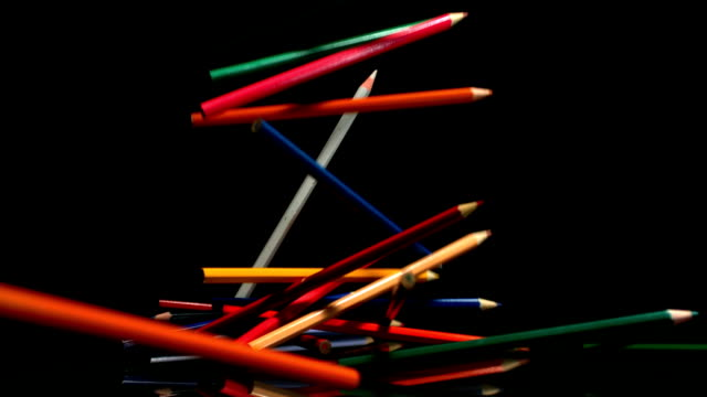 Colouring pencils falling on black background video