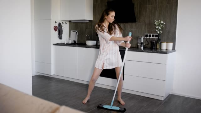 comedian woman is dancing with mop during cleaning kitchen room in her house on holidays, singing and moving funny video