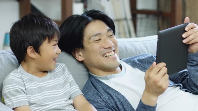 快適な父と息子のタブレット コンピューターのゲームをプレイ - タブレット端末点の映像素材/bロール