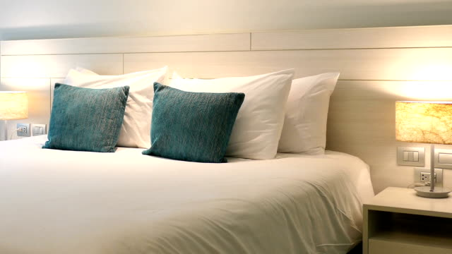 Comfortable pillow on bed decoration in hotel bedroom interior video
