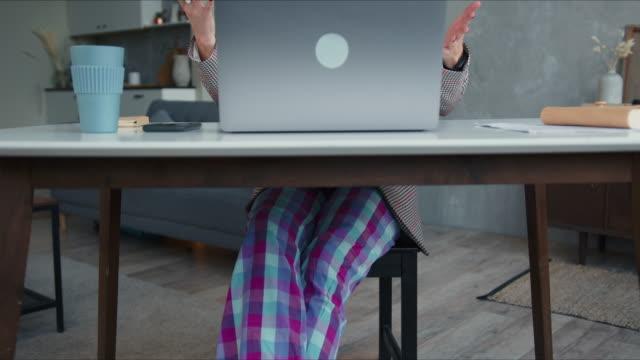 bekväm självisolering livsstil. ung lycklig affärskvinna i pyjamas byxor med hjälp av laptop webbkamera för att arbeta hemifrån. - byxor bildbanksvideor och videomaterial från bakom kulisserna