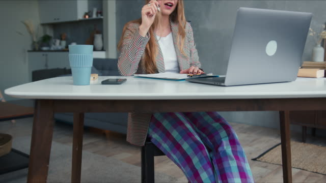 comfortable work from home. young blonde teacher woman in pajamas pants using laptop video call to lead classes online. - pajamas stock videos & royalty-free footage