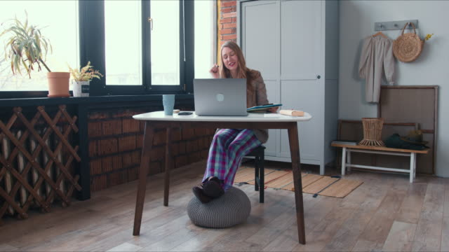 Comfortable work from home. Young Caucasian business woman in pajamas pants working online using laptop video call app. video