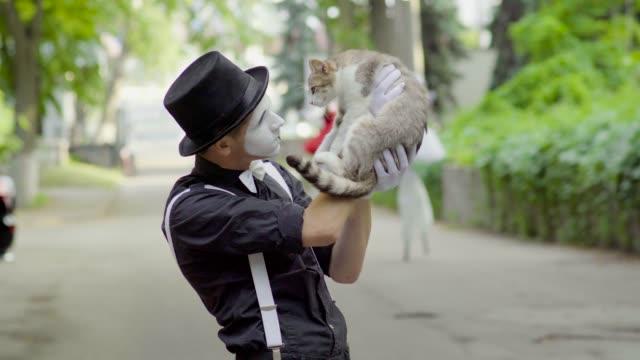 comic mime joking with cat on the street - гримировальные краски стоковые видео и кадры b-roll